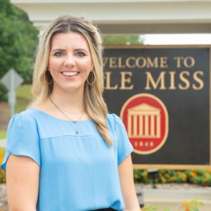 """Katie next to an entrance sign that says """"Welcome to Ole Miss"""""""